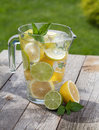 Pitcher with homemade lemonade on wooden table Royalty Free Stock Photos