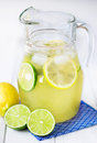 Pitcher with lemonade full of lemon and lime ice Royalty Free Stock Photo