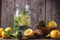 Pitcher of lemonade glass homemade served with whole and sliced lemons limes and mint over wooden table with wooden background Stock Photography