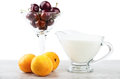Pitcher of yogurt glass with cherries and apricots on table Royalty Free Stock Photo