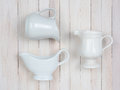 Pitchers on white closeup of three ceramic a rustic whitewashed wood table high angle shot in horizontal format Stock Image