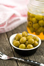 Pitted green olives in bowl on wooden table Stock Photography