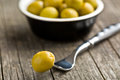 Pitted green olives on wooden table Stock Images