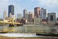 Pittsburgh north shore view yellow painted iron suspension bridge cross the icey allegheny river toward downtown pennsylvania Stock Photography