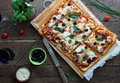Pizza with bbq sauce chicken and bacon on a rustic table Stock Image
