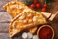 Pizza calzone closeup on a paper and ingredients. Horizontal top Royalty Free Stock Photo