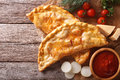 Pizza calzone on a paper and ingredients. horizontal top view Royalty Free Stock Photo