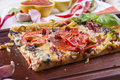 Pizza close up of the just baked homemade with tomato salami slices and olives placed on brown cutting board Royalty Free Stock Images