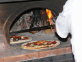 Pizza cooked in wood oven pizzaiolo at work italian pizzeria Stock Photos