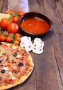 Pizza and ingredients on the kitchen table Royalty Free Stock Photography