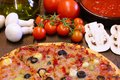 Pizza and ingredients on the kitchen table Stock Photography