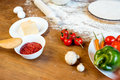 Pizza ingredients, vegetables and dough on wooden tabletop