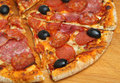 Pizza with italian meats salami and black olives Royalty Free Stock Image