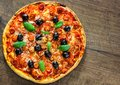 Pizza with Mozzarella cheese, salami, pepper, pepperoni, Tomatoes, olives, Spices and Fresh Basil. Italian pizza on wooden backgro Royalty Free Stock Photo