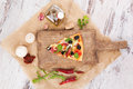 Pizza piece and pizza ingredients culinary cooking on wooden kitchen board with various toppings fresh herbs olive oil garlic Royalty Free Stock Image