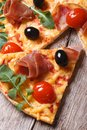 Pizza with prosciutto tomatoes and arugula olives closeup pieces of on wooden background top view vertical Royalty Free Stock Photos
