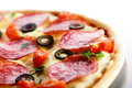 Pizza with salami and black olives macro Royalty Free Stock Photos