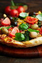 Pizza with spinach, olives and cherry tomatoes Stock Image