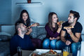 Pizza time for friends having fun and eating at night selected focus on face of men on left side Stock Photos