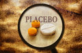 Placebo effect of tablets under a magnifier and word on grunge background Royalty Free Stock Photos