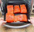 Placing Salmon into Oven for Baking Royalty Free Stock Photo