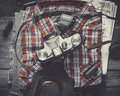 Plaid shirt pair of jeans and old film camera top view vintage stylized Stock Images