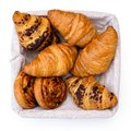 Plain and chocholate croissants and rasin danish pastry swirls in linen basket isolated on white from above