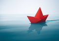 Plain sailing red paper boat on water with waves and ripples Stock Photos