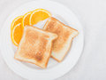 Plain toas tgarnished with orange slices unbuttered toast on a white plate garnished of navel Stock Photos