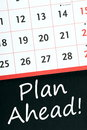 Plan ahead a standard wall calendar on a blackboard with the phrase written beneath it Royalty Free Stock Photos