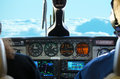 Plane cockpit view while in flight small twin turbo engine piper with gauges lit up and fluffy white and blue clouds the window Stock Photo