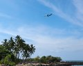 Plane coming landing over tropical island Stock Photos