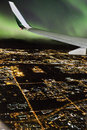 Plane flight during northern lights the view from a commercial airplane window showing a city scene underneath and the aurora Royalty Free Stock Photography