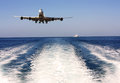 Plane over the sea large passenger airplane flying above surface at low altitude Royalty Free Stock Images