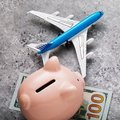 Plane, piggy bank and one hundred dollars on the table. Concept on the topic of saving money for air travel Royalty Free Stock Photo