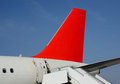 Plane with red tail, boarding ladder.  Blue sky. Success Royalty Free Stock Photo