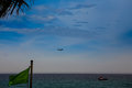 Plane in sky above sea fishing boat green banner on foreground aircraft blue azure with and Stock Photography