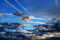 Plane trails above clouds by blue hour Royalty Free Stock Photo