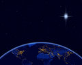 Planet earth and Christmas star in night sky Royalty Free Stock Photo