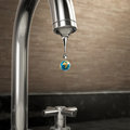 Planet earth water drop coming out of the tap ecology and sustainability Stock Photo