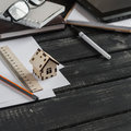 Planning of the construction of a house. Office desk with business objects - open notebook, tablet computer, glasses, ruler, pen a Royalty Free Stock Photo