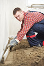 Plasterer concrete worker at floor work indoor cement topping with float Royalty Free Stock Images