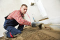 Plasterer concrete worker at floor work indoor cement topping with float Stock Photo