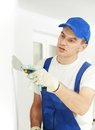 Plasterer with putty knife at wall filling home improvement handyman worker working on apartment Stock Photos