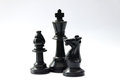 Plastic black chess pieces - king, bishop, knight - and white background Royalty Free Stock Photo