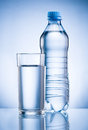 Plastic bottle and glass of drinking water on blue back background Stock Image