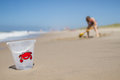Plastic bucket on sand beach focus is with red crab illustration blurred background with young girl digging in the girl is wearing Stock Photography