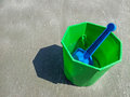 Plastic bucket shovel summer beach toy green on sand Stock Photo