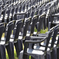 Plastic chairs dark blue waiting for audience at an open air event on a green lawn Stock Photo