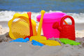 Plastic children toys on the beach sand Stock Photos